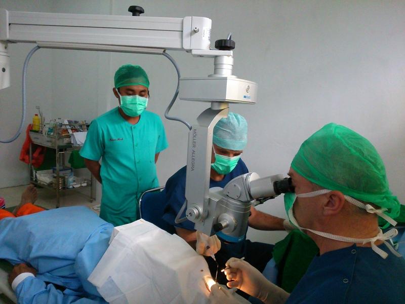 Artsen operend aan oog met microscoop